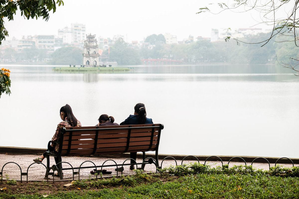 People seat bench Hoan Kiem Lake Hanoi Vietnam