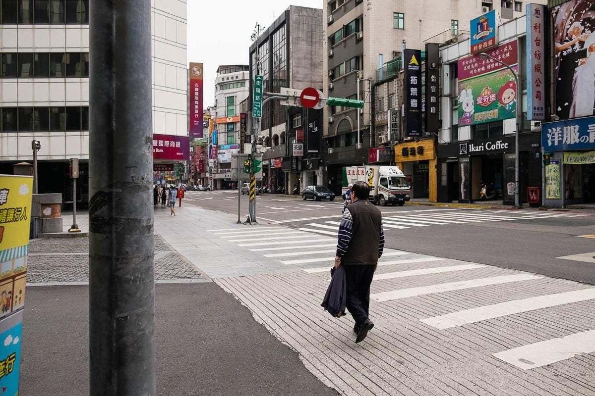 Taiwanese man crosses the street. Taipei, Taiwan.