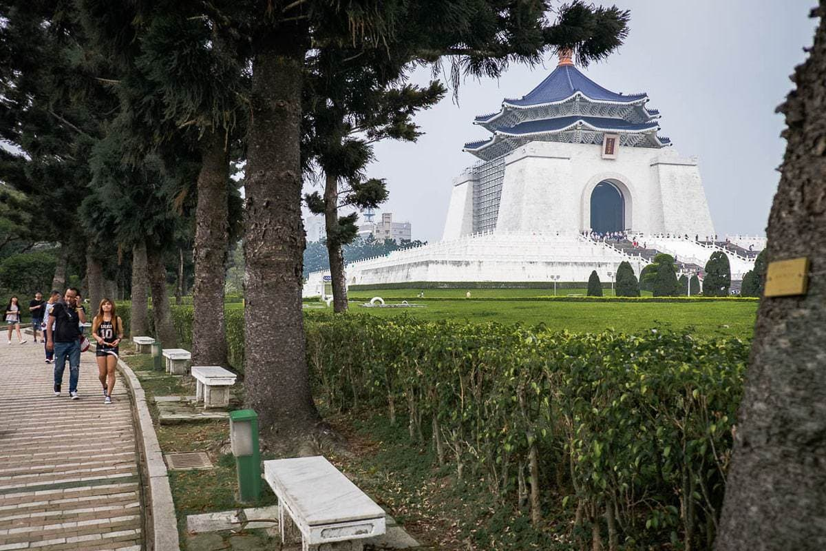 People walk in the park next to the National Chiang Kai-shek Memorial Hall. Taipei, Taiwan.