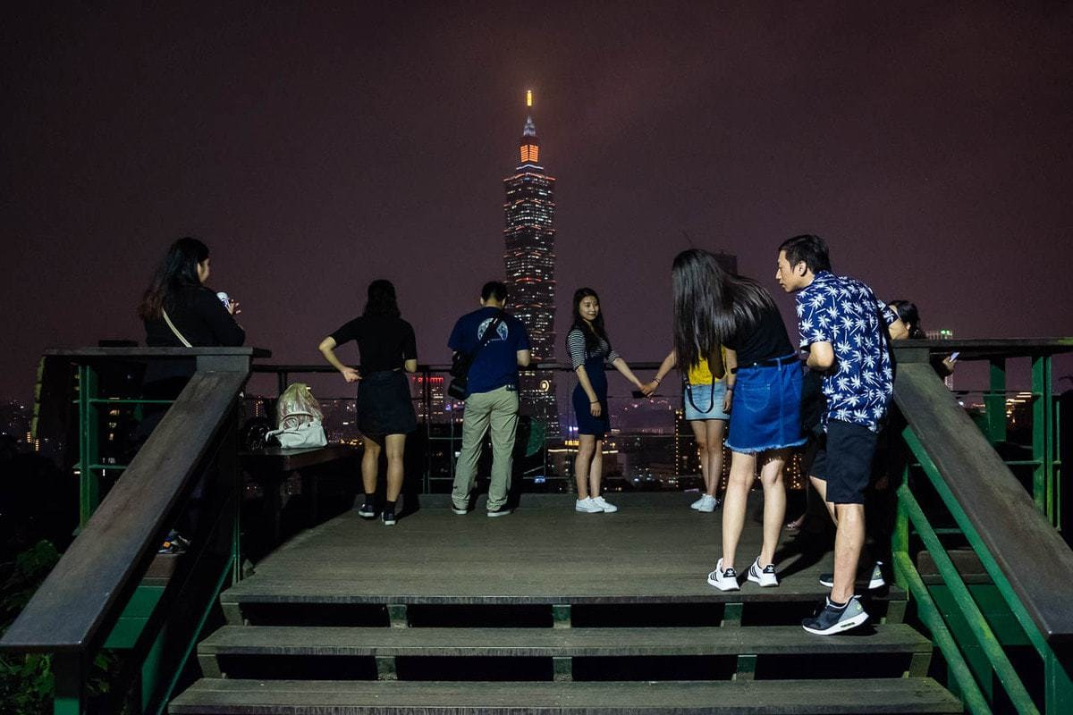 Young people observe the TAIPEI 101 Building at night from Elephant Hill. Taipei, Taiwan.