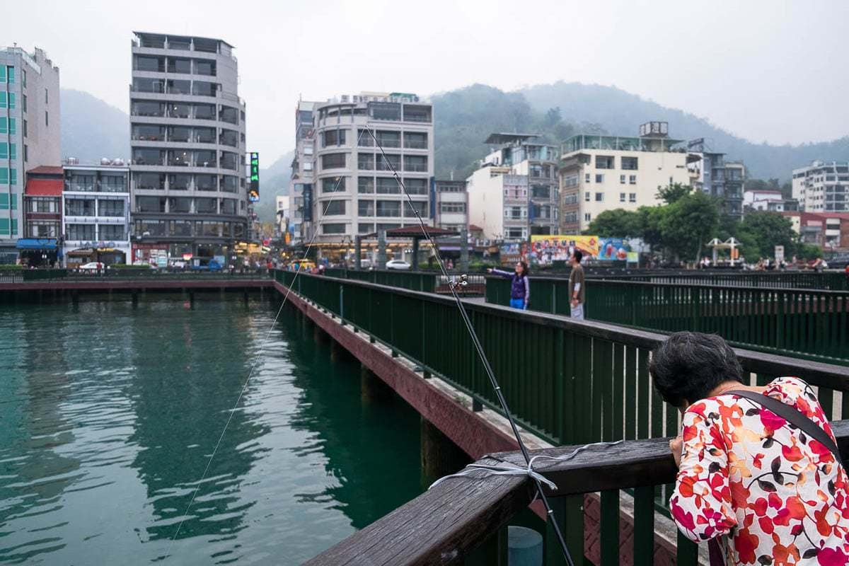 Woman fishes at Ita Thao (Yi Da Shao) Wharf. Sun Moon Lake, Taiwan.