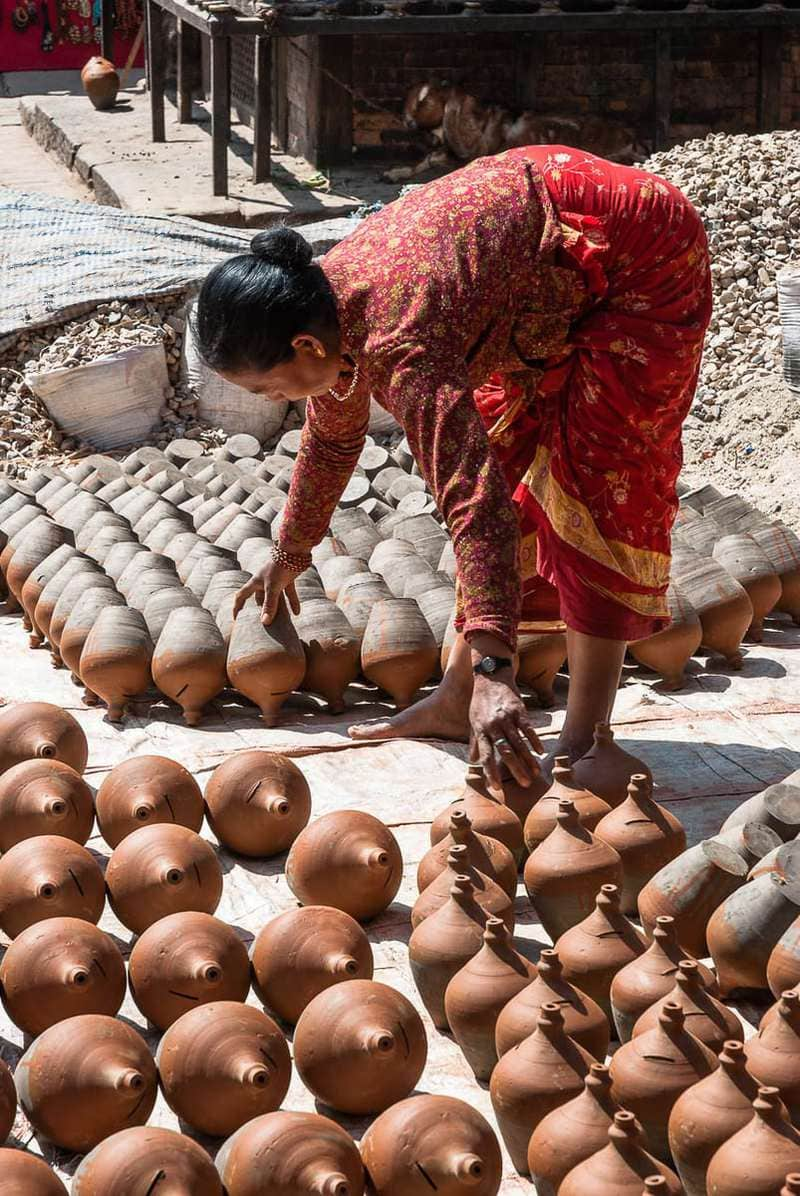 Nepalese woman sets money boxes or piggy banks at Pottery Square, Bhaktapur. Kathmandu Valley, Nepal.