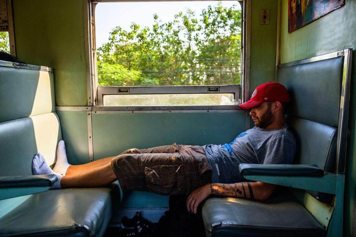 Napping on the Kanchanaburi - Bangkok train, Thailand.