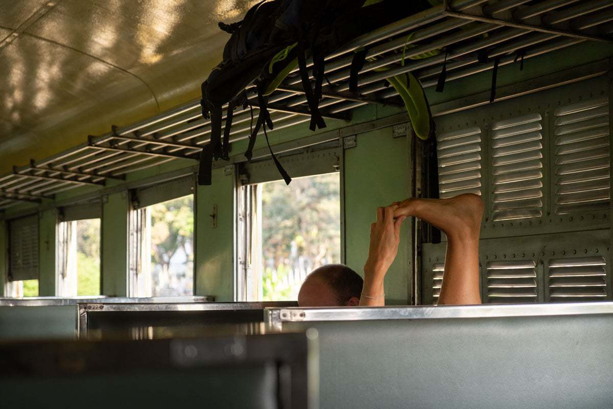 Stretching on the Kanchanaburi - Bangkok train, Thailand.