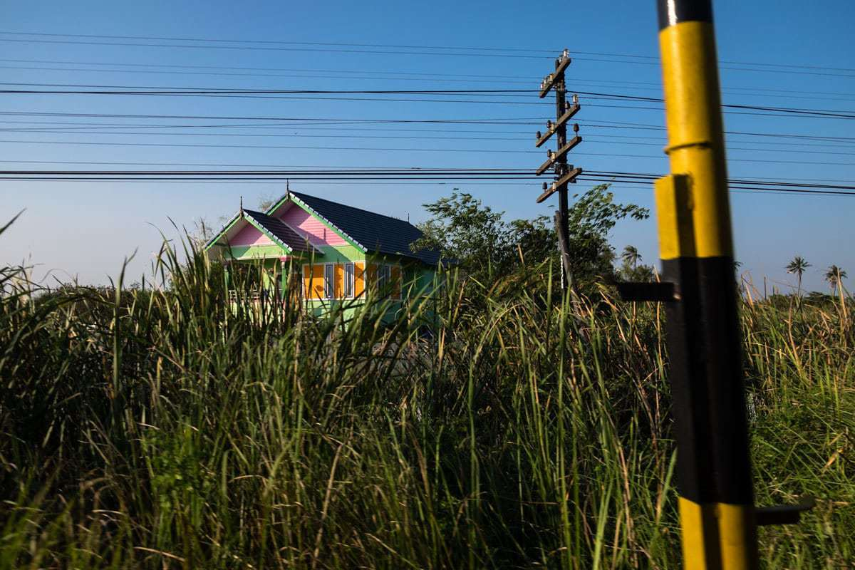 A colourful little house in the countryside seen from the Bangkok - Kanchanaburi train, Thailand.