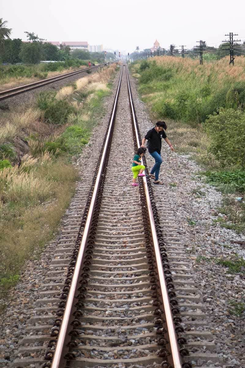"Mother with child ""safely"" crossing the railroad tracks, Thailand."