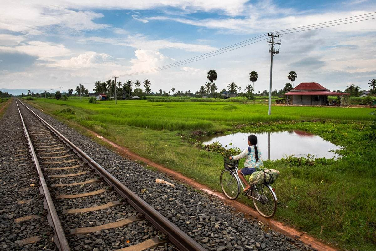 Khmer child cycles by the railway near a level crossing. Kampot, Cambodia.