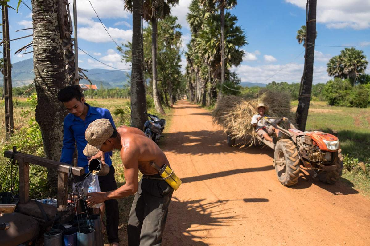 A customer with empty plastic water bottles buys some of the sap off the palm sugar harvester.