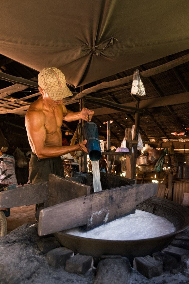 He empties the containers with the collected sap into a large pan and it gets filtered to eliminate any residue.