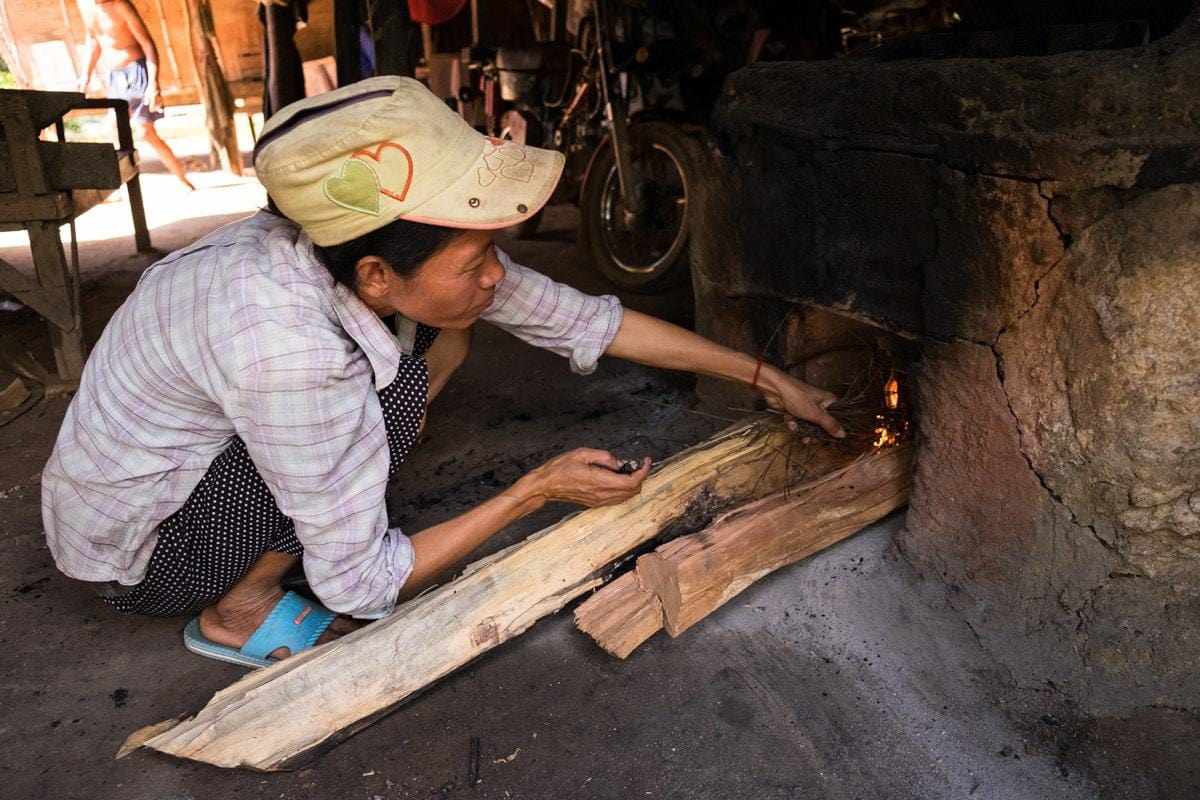 His wife sets the fire under the large pan.