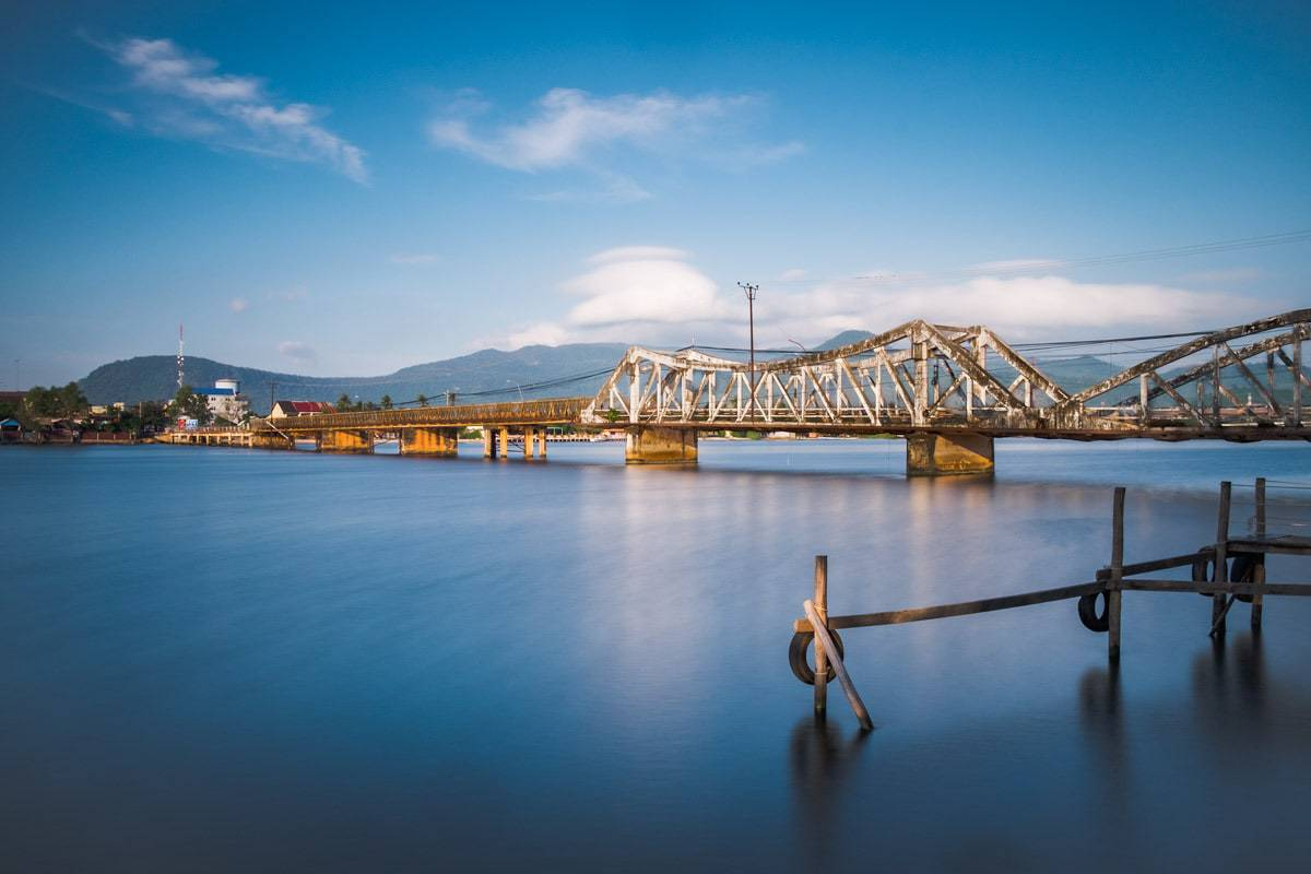 Old French bridge over Kampot River in the morning. Kampot, Cambodia.
