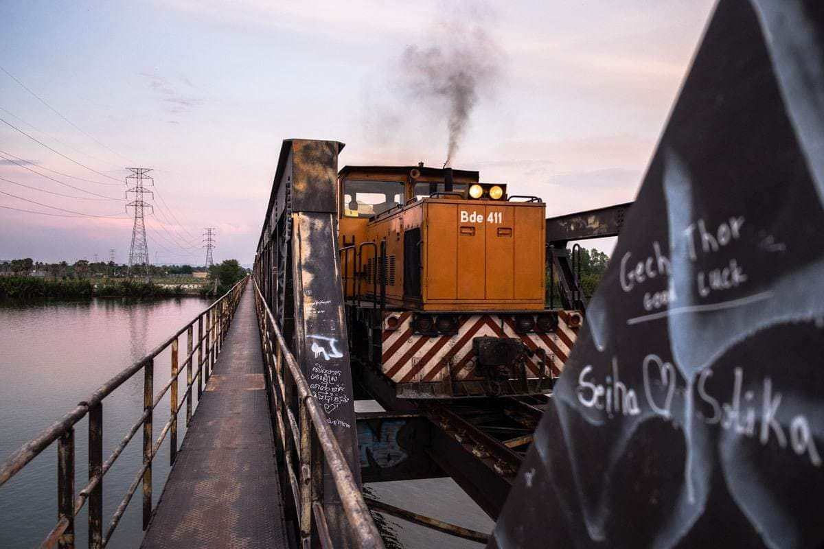 A freight train on the railway bridge over the Kampot River. Kampot, Cambodia.