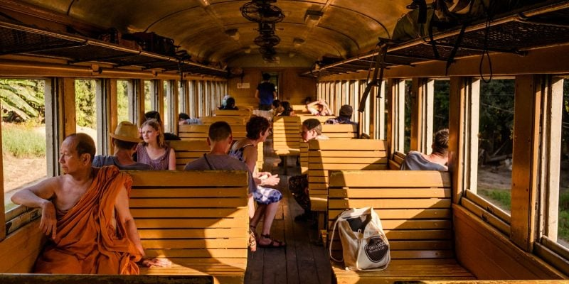 Inside train photography - A train journey in Thailand from Bangkok to Kanchanaburi. Passengers on wooden seats.