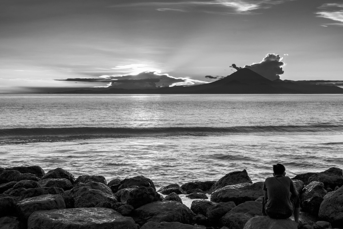 Man seats on rocks and looks at Mount Agung at sunset. Lombok Island, Indonesia.