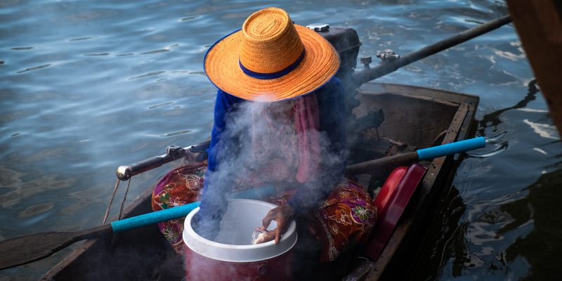 Barbecue chicken seller on a small boat on Bang Luang Canal. A genuine and quiet floating market in Bangkok.