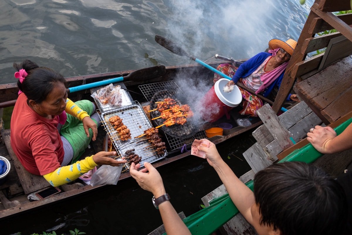 Barbecue chicken sellers on a boat serve people on the banks of Bang Luang Canal.