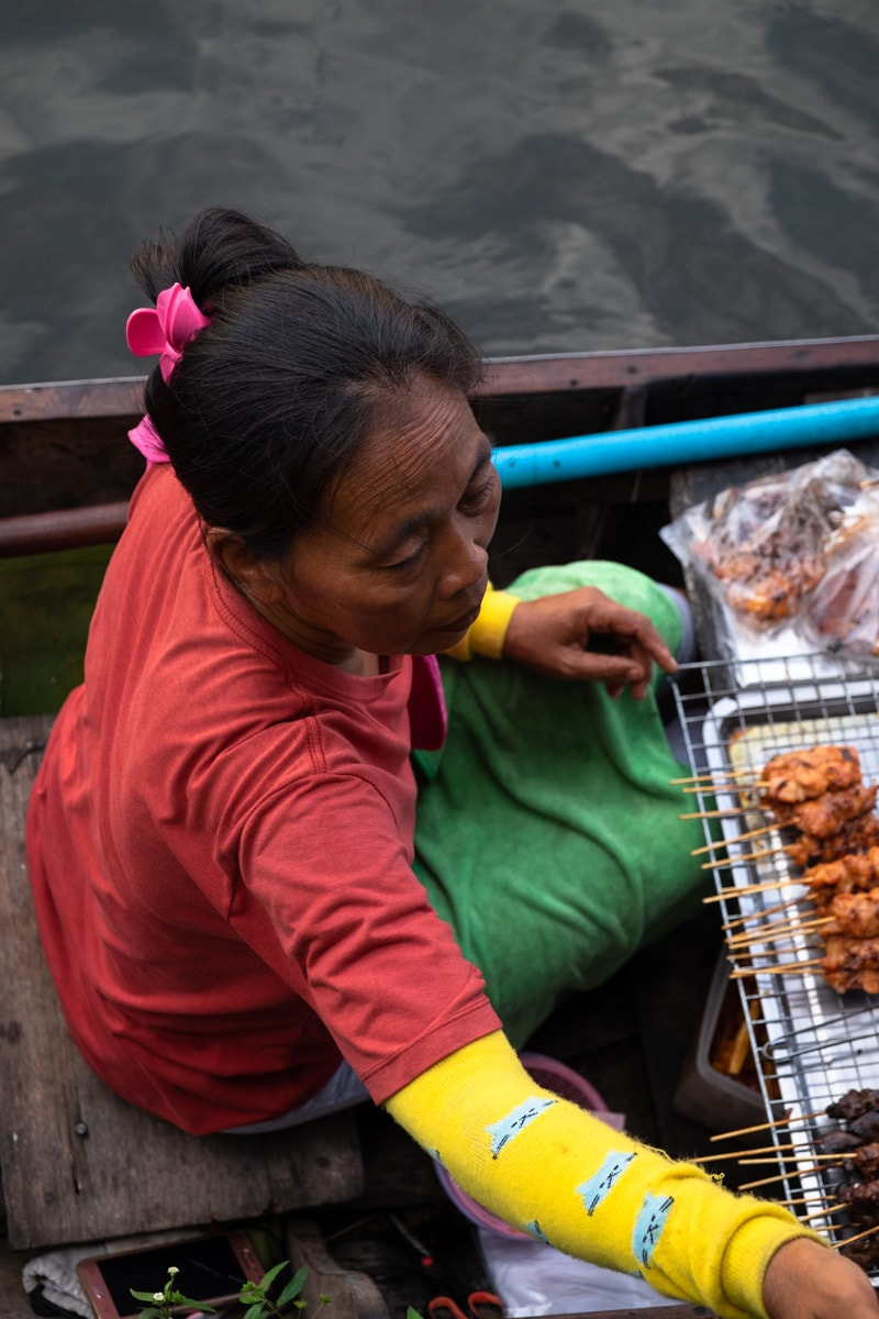 Close up of a barbecue chicken seller on a boat serving people on the banks of Bang Luang Canal.