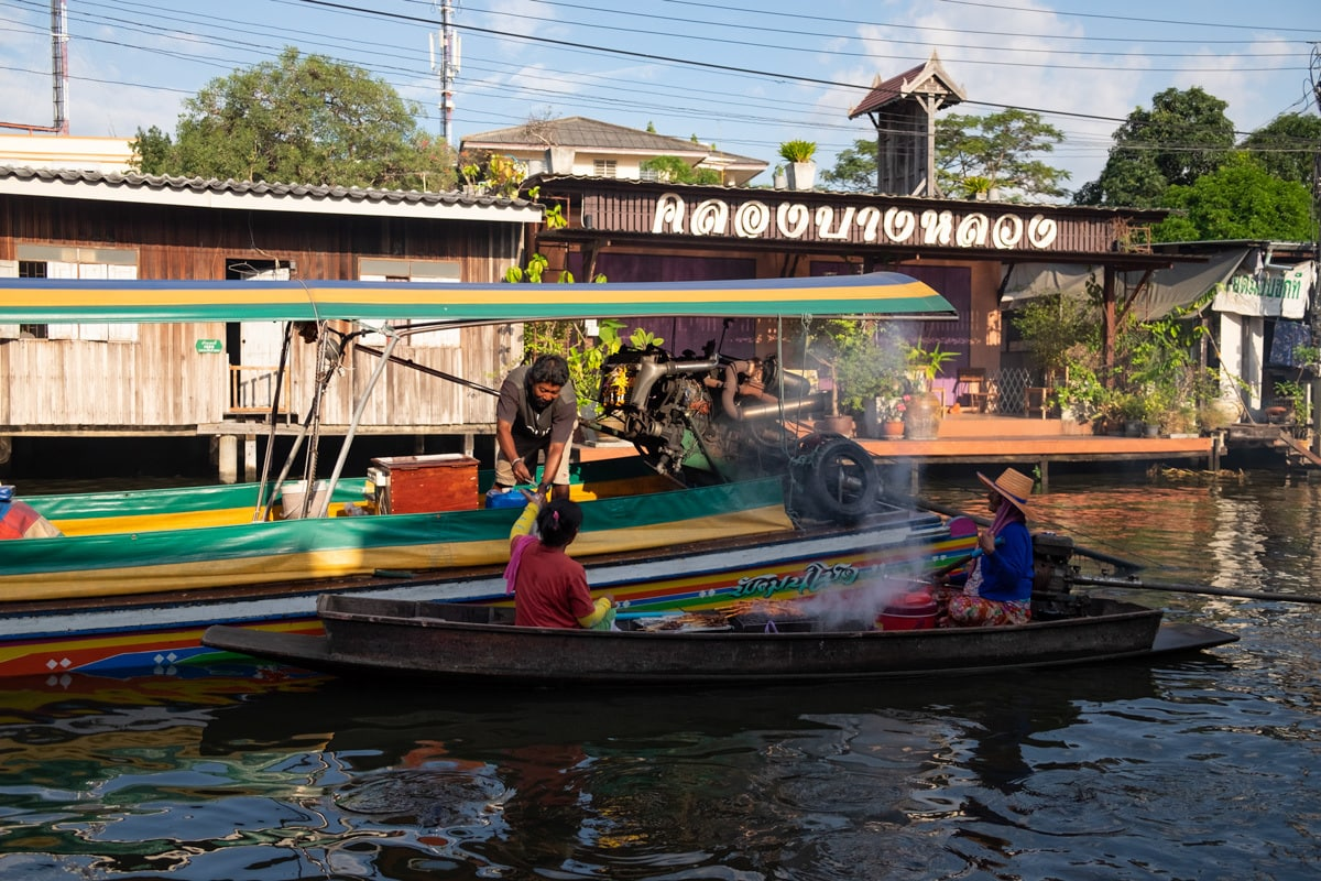 Barbecue chicken sellers serve a long-tail boat driver.