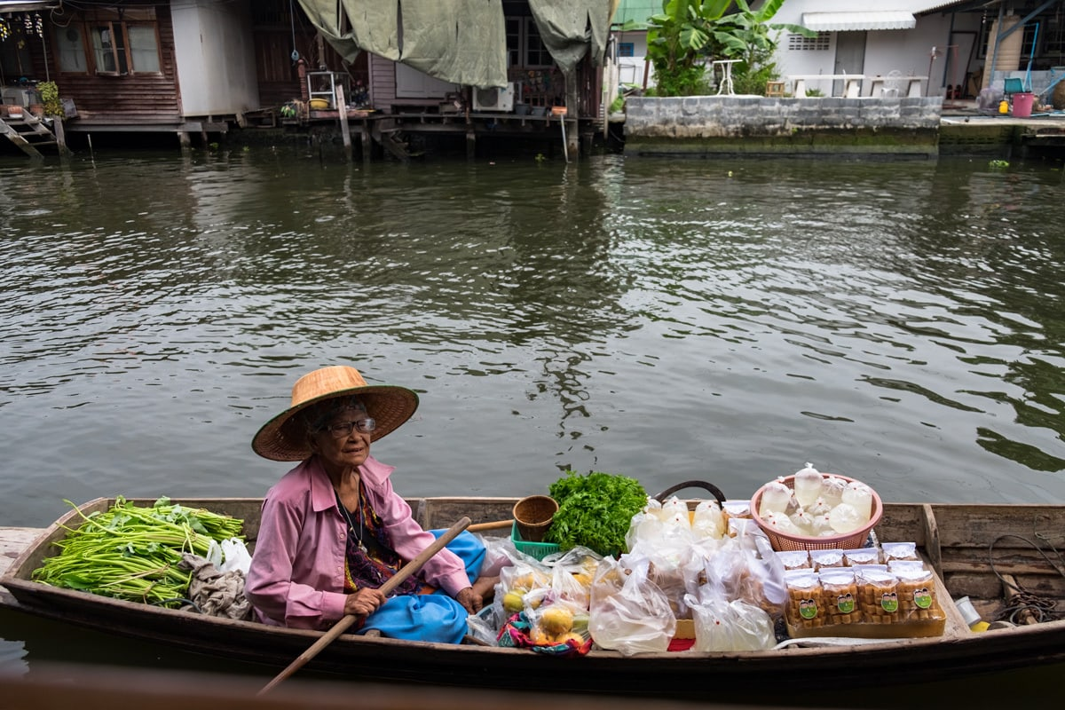 Thai snack vendor on a boat awaits customers at Bang Luang Canal.