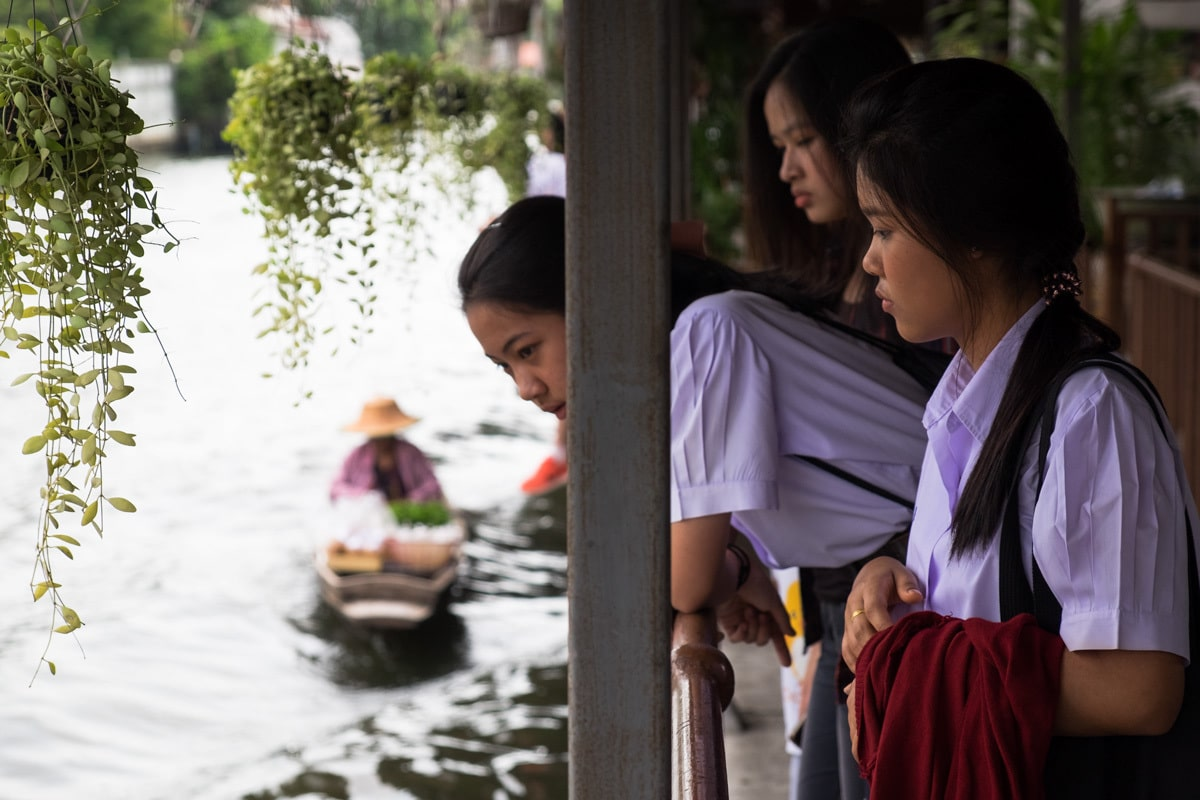 High school students watch people's daily life at the floating market.