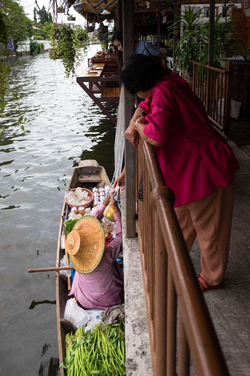 Fruit and veg seller on a boat gives change to customers.