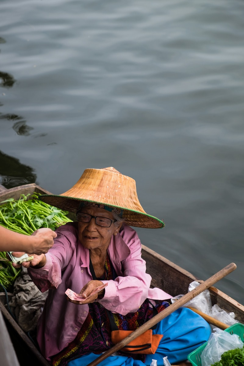 Fruit and veg vendor on a boat gives change to customer.
