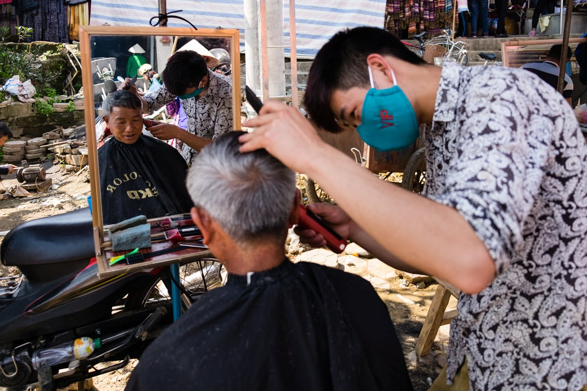 A Vietnamese man has his haircut done at one of the open-air barber stalls at Bac Ha market in Northern Vietnam.
