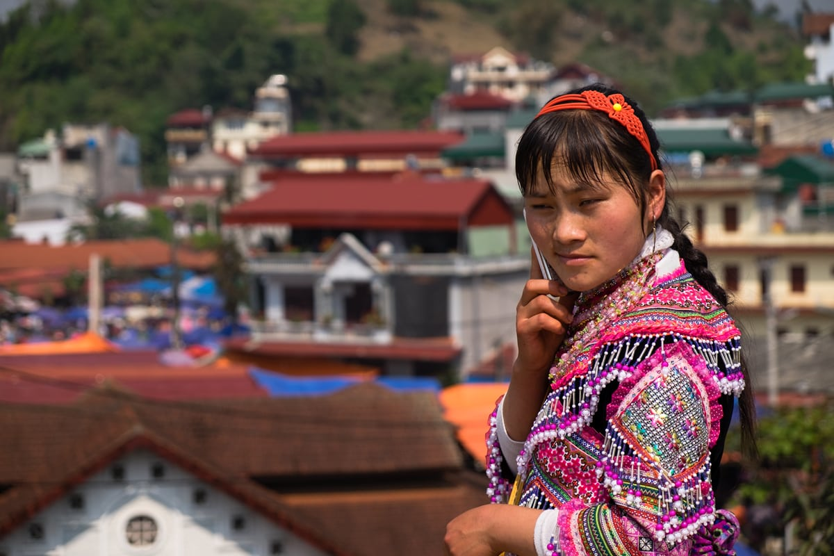 A Flower H'Mong woman speaks on the phone at Bac Ha market in Northern Vietnam.