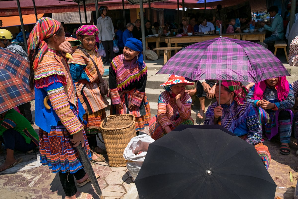 Hill tribe Flower H'Mong women chat at Bac Ha market, Vietnam.