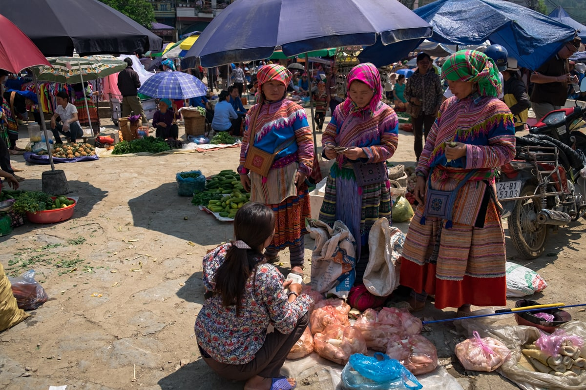 Hill tribe Flower H'Mong women buy bamboo shoots at Bac Ha market, Vietnam.