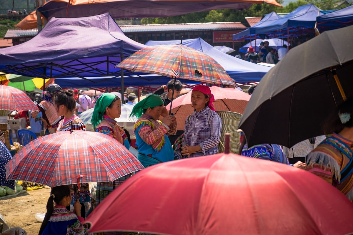 Umbrellas and hill tribe Flower H'Mong people at Bac Ha market. Vietnam.