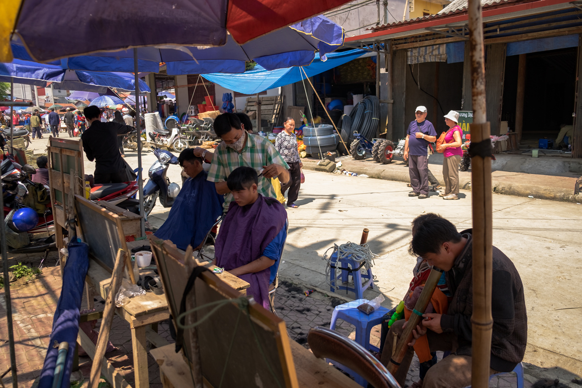 Vietnamese young men have their haircut done at one of the open-air barber stalls at Bac Ha market in Northern Vietnam.