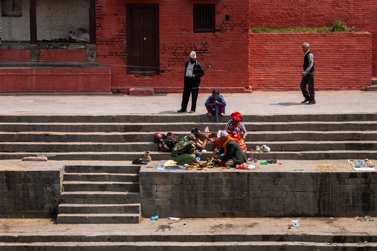 Nepalese family seat on the bank of the Bagmati River at Pashupatinath Temple in Kathmandu, Nepal.