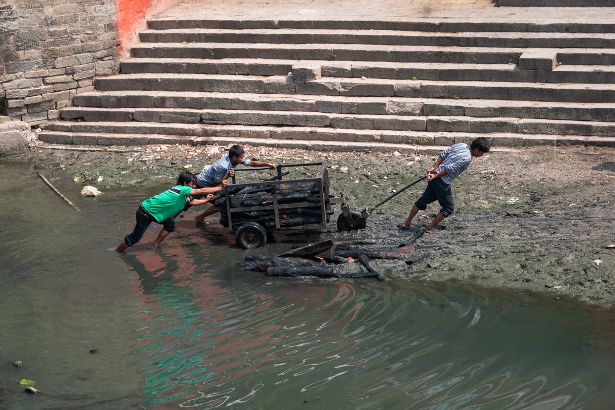 Three young Nepali men drag wood for cremations on the Bagmati River at Pashupatinath Temple in Kathmandu, Nepal.