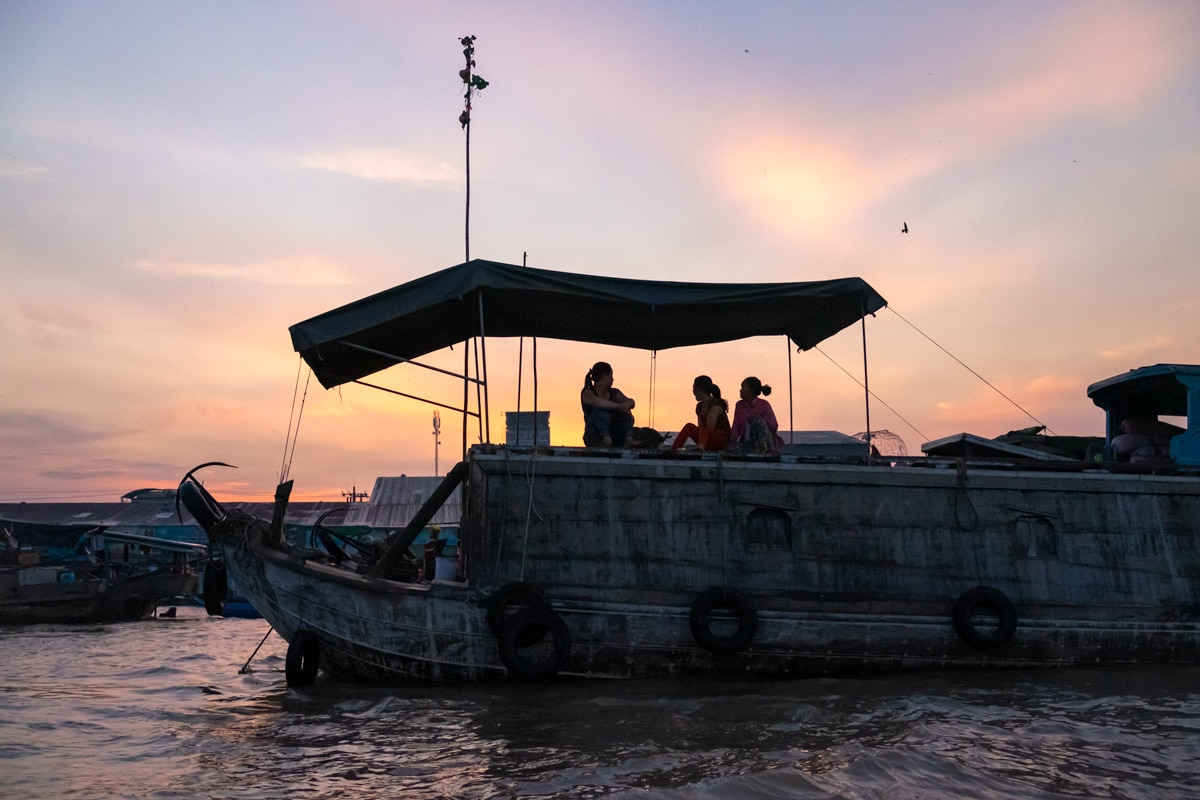 Three Vietnamese veg sellers enjoy the sunrise on their boat at Cai Rang floating market on the Mekong Delta. Can Tho, Vietnam.