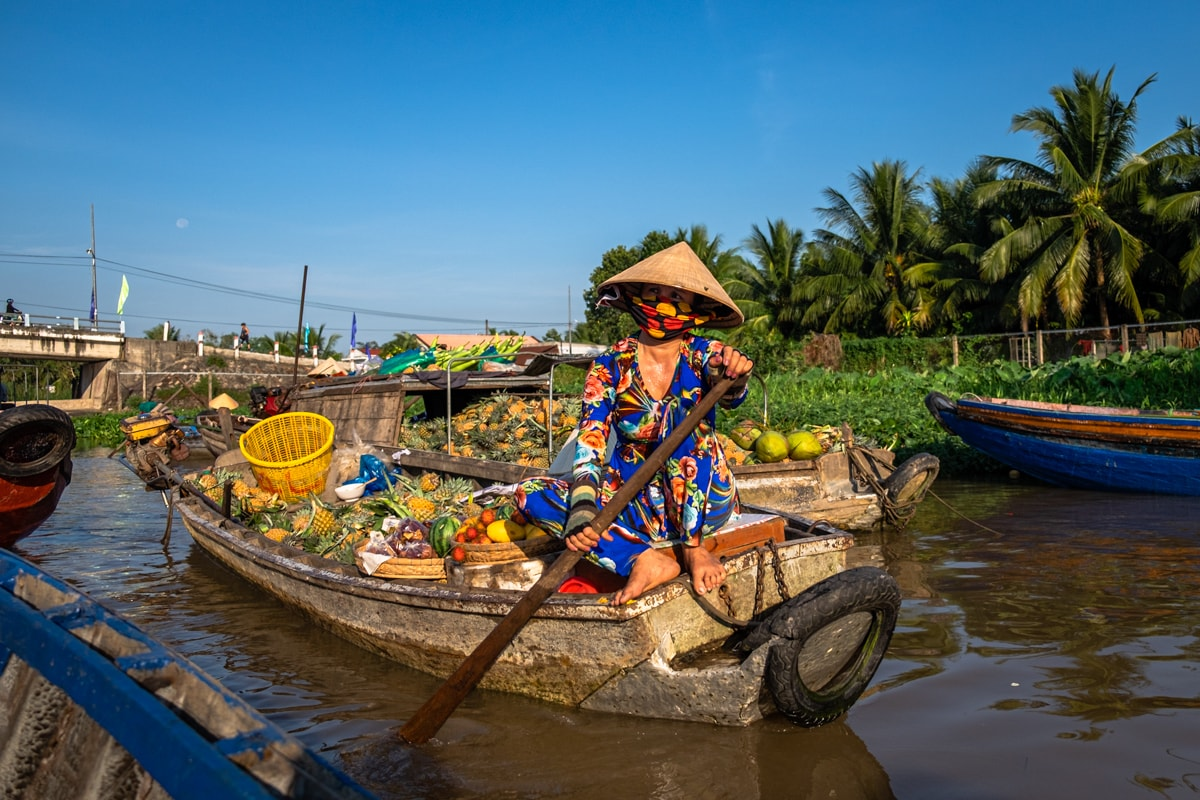 Vietnamese fruit seller sits on her boat on Phong Dien floating market. Mekong Delta, Can Tho, Vietnam.