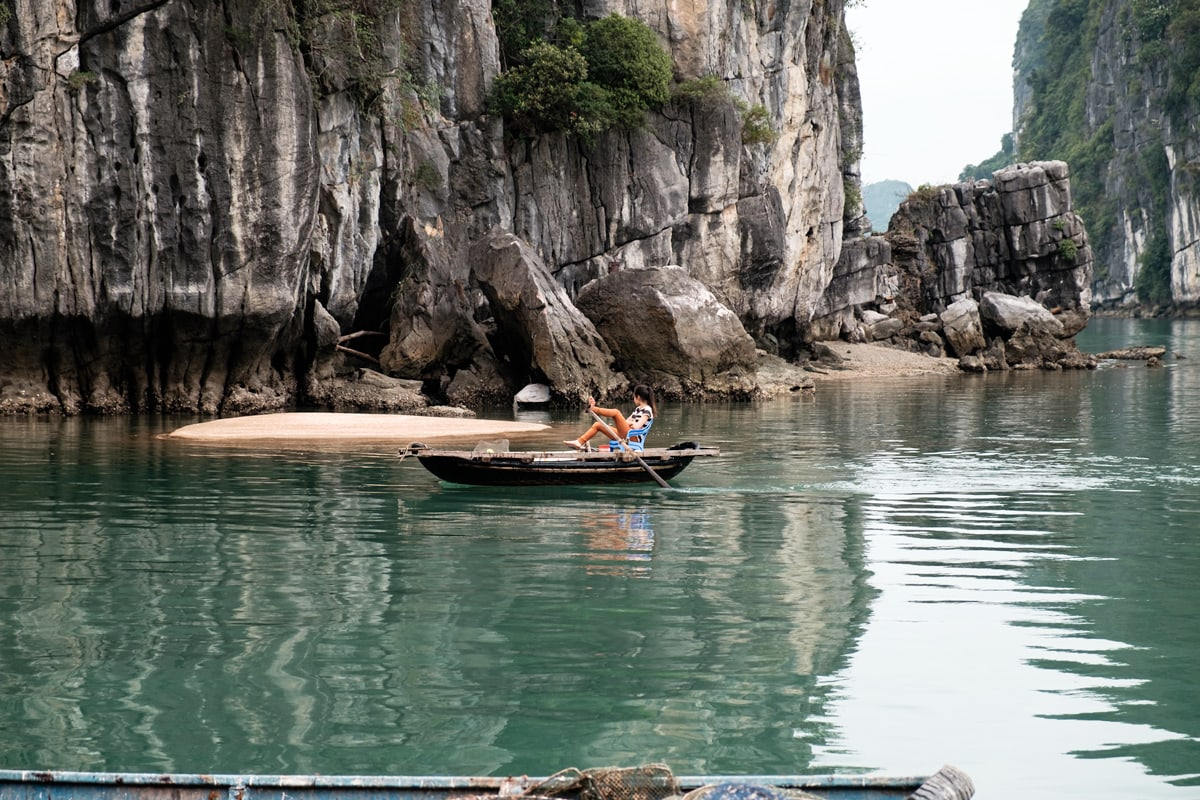 Vietnamese girl rows her boat by her feet in Halong Bay, Vietnam.