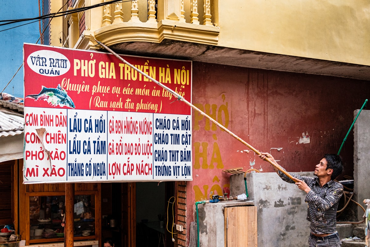 Vietnamese decorator uses a handmade extension pole paint brush to decorate a balcony. Sapa, Vietnam.