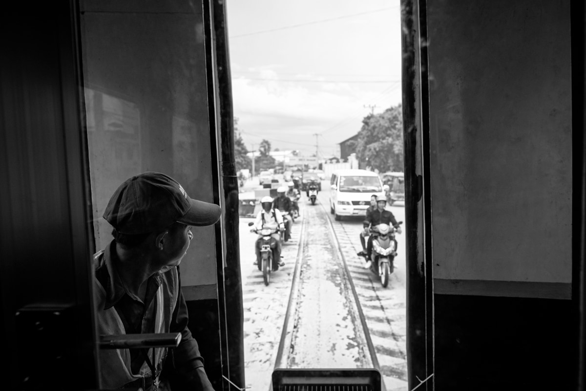 View of the traffic from the back of the train from Phnom Penh Railway Station to Phnom Penh International Airport. Cambodia.