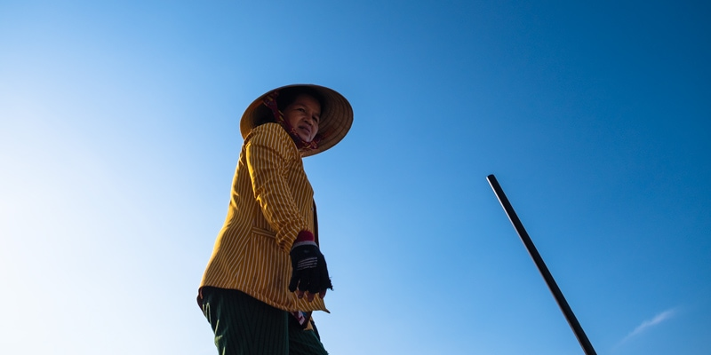 Pineapple & wax gourd seller stands on her boat on Phong Dien floating market. Can Tho, Mekong Delta, Vietnam.
