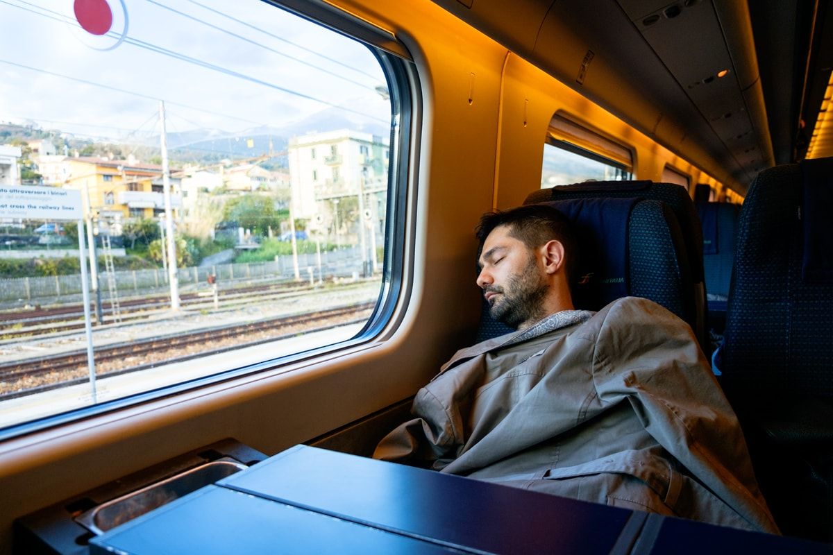 Italian man has a nap on the Rome-Reggio Calabria High Speed Train. Italy.