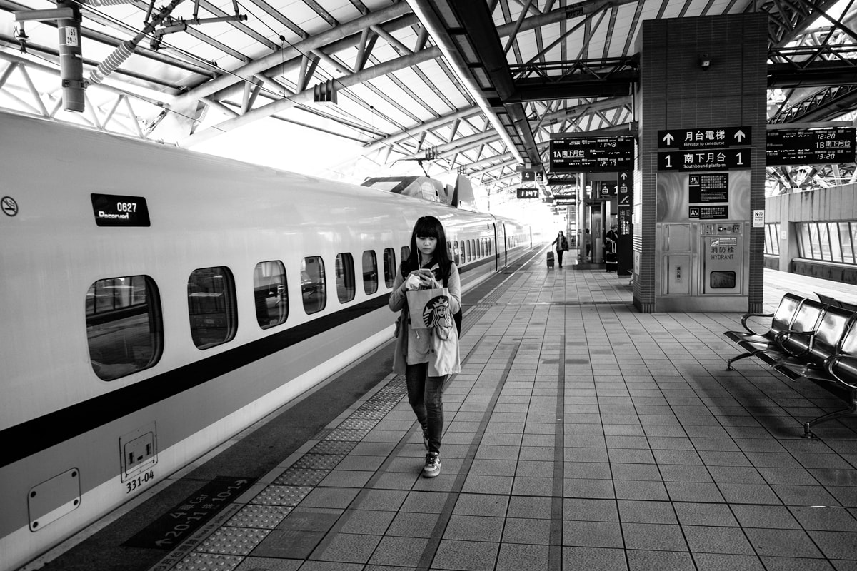 Taiwanese girl has just got off the Taichung-Taipei High Speed Train. Taipei train station, Taiwan.