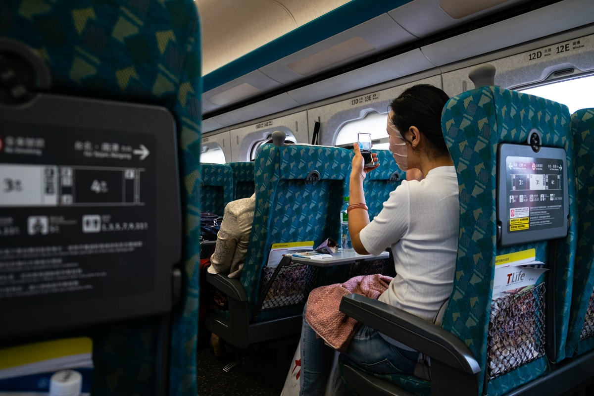 Taiwanese girl applies a face mask sheet. Taichung-Taipei High Speed Train. Taiwan.