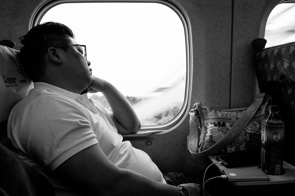 Taiwanese man has a nap on the Taichung-Taipei High Speed Train. Taiwan.