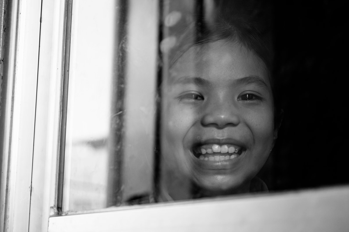 Cambodian child smiles for my camera on a train from Kampot to Phnom Penh. Cambodia.