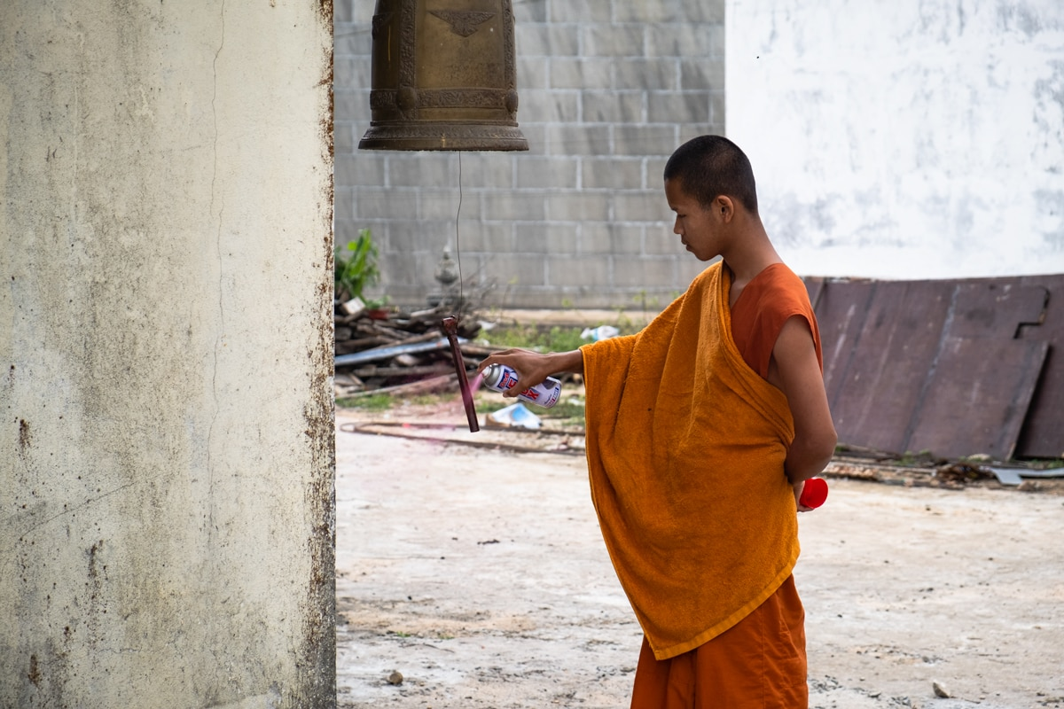 Cambodian novice monk at Wat Sampov Pram Pagoda colour sprays a Buddhist bell. Bokor Mountain. Kampot, Cambodia.