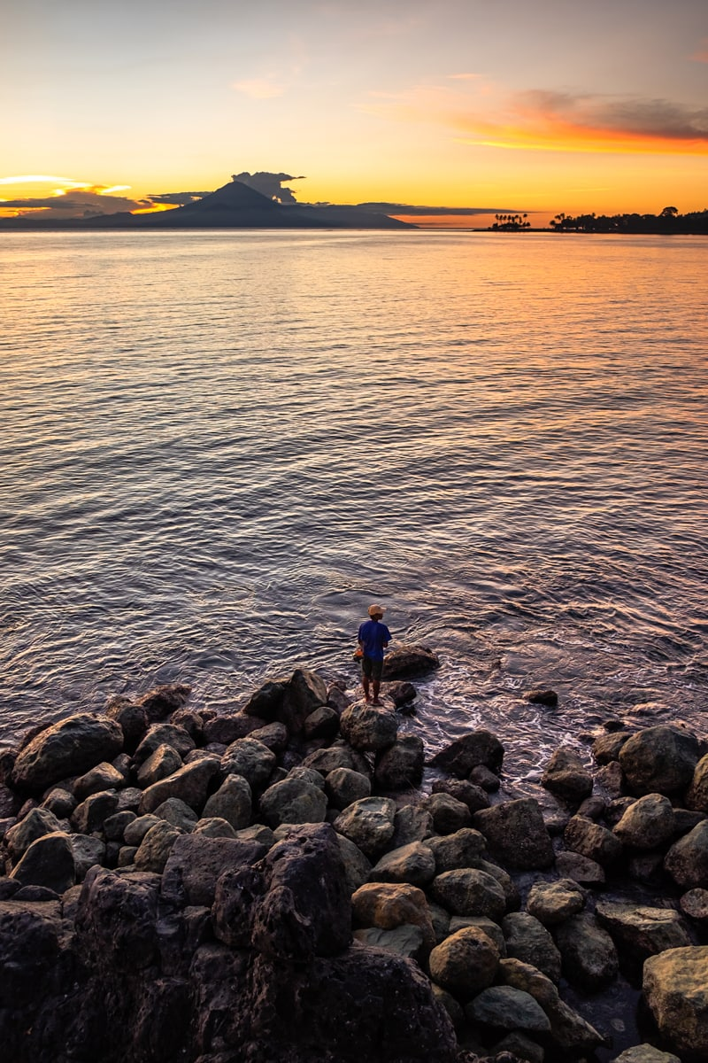 Fisherman on rocks fishes at sunset. Senggigi Beach on Lombok Island, Indonesia.