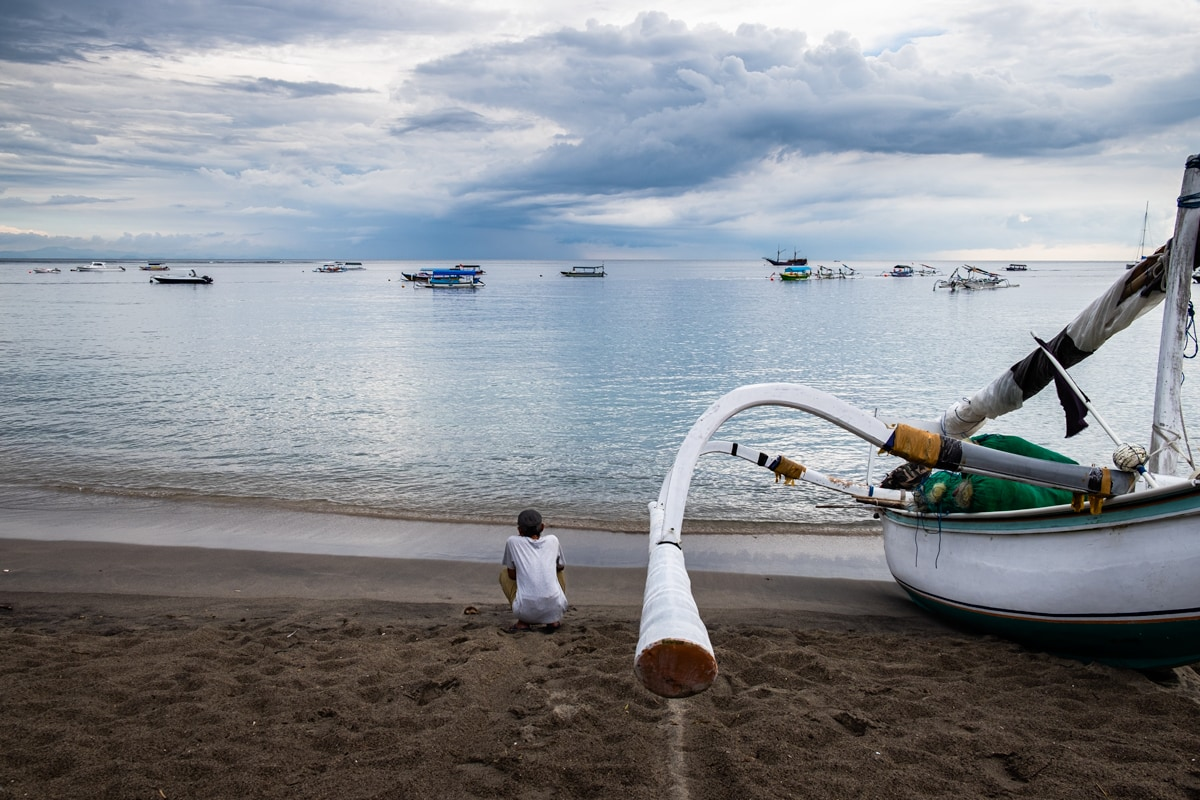 Traditional Indonesian boat and man on the beach at Senggigi on Lombok Island, Indonesia.