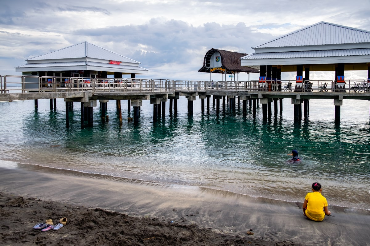 Woman enjoys a swim at Senggigi Pier. Lombok Island, Indonesia.