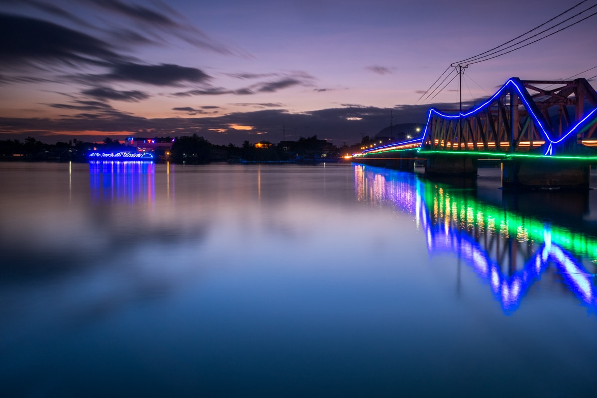 Cityscape of Kampot River with the old French bridge all illuminated at dusk. Kampot, Cambodia.